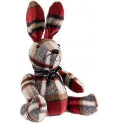 A sitting rabbit doorstop made with a red tartan based faux suede fabric