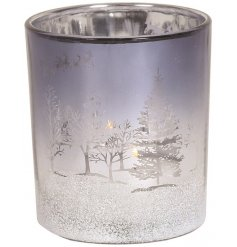 A beautiful little silver coloured candle holder, featuring a metallic winter scene decal