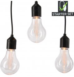 Set with a filament LED inspired look these warm glowing bulbs strung along a chunky black wiring