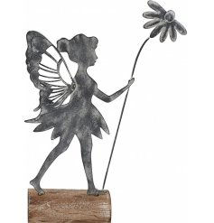A rustic metal fairy decoration set upon a wooden base.