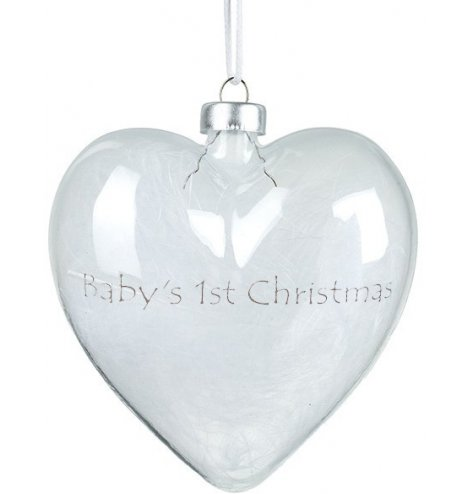 A stunning glass heart decoration filled with white feathers and decorated with a silver 'Baby's 1st Christmas' slogan.