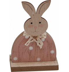 A cute standing wooden bunny decoration with a pink polka dot dress