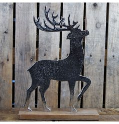 A beautifully simple ornamental reindeer set upon a natural wooden block