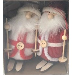 Pair of skiing santa figures in complementary knitted outfits, boxed for transport