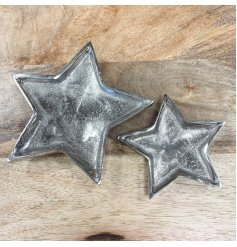 A rustic silver metal star dish with a hammered finish. A charming decorative accessory.