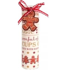 A beautifully decorated glass candle tube with a gingerbread cookie fragranced candle.