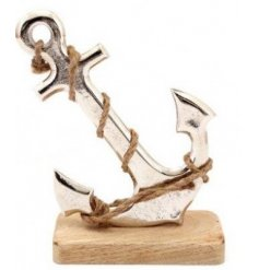 A large ornamental silver anchor rested on a natural wooden block base