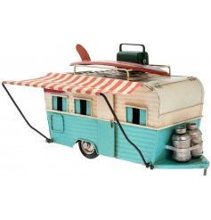 A vintage inspired camper van complete with a bright blue decal and topped with a surf board