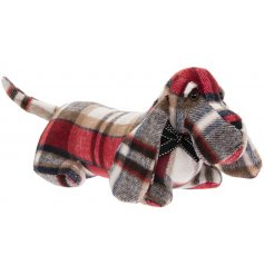 A  lounging dog doorstop made with a red tartan based faux suede fabric