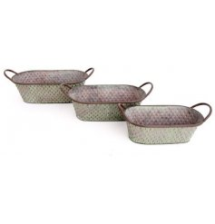 An overly distressed decorative set of sized metal troughs, each featuring a tarnished green diamond ridge decal