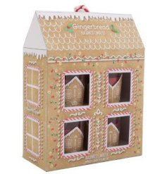 A gingerbread house shaped gift set filled with 4 scented candle pots and a matching candle plate
