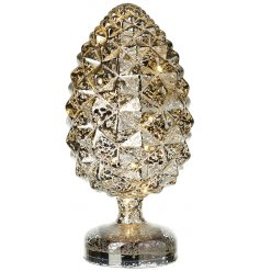 a large glass fir cone ornament with an added mottled effect and warm glowing centre