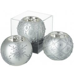 a mix of silver glass tlight holders in a bauble shape, each decorated with a pretty pattern