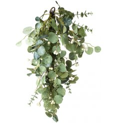 A large hanging branch full of artificial eucalyptus foliage and added berries and extras