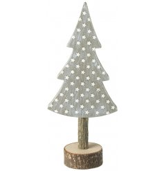 A whitewashed wooden tree decoration with added stars and a wooden block base