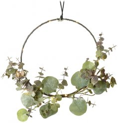 A large hanging hoop entwined with warm glowing LED lights and finished with a pretty Eucalyptus branch
