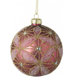 a glass bauble in a blush pink tone, covered with glittery accents and patterns