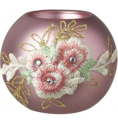 A beautiful matte pink glass tlight holder decorated with an embroidery inspired floral print