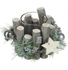 A small woodland inspired tlight holder decorated with added baubles, glitter and stars