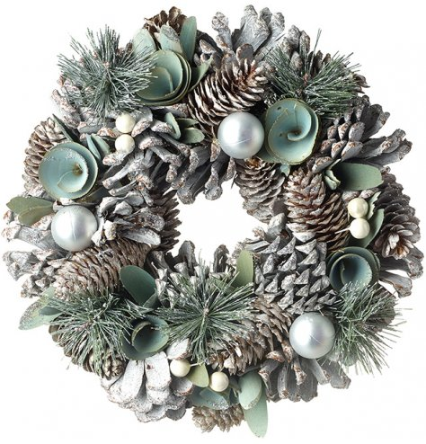 A rounded wreath decorated with a woodland floor inspired foliage decal and trending sage green colouring