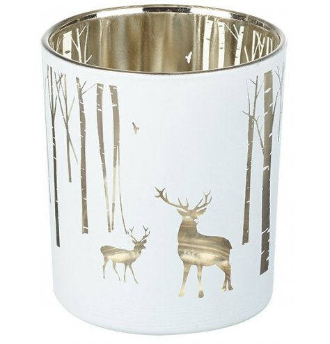 A silver lined glass tlight holder with an etched woodland decal across the front