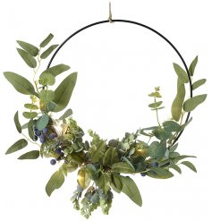 A simple metal hoop wreath entwined with green leaf foliage and added blueberries
