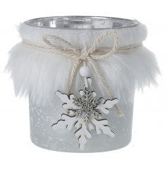 A glass tlight holder with a faux fur trimming and snowflake charm hanger