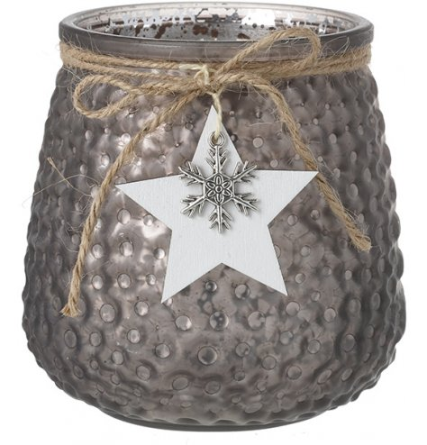 A decorative mottled glass candle holder set with a ridged decal and hanging star and snowflake charm