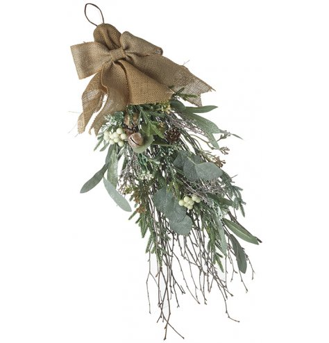 A bouquet of winter foliage with a frosty glaze, hung in a jute bow.