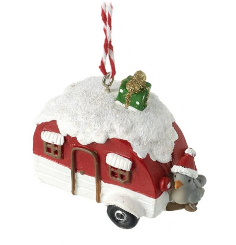 A snowy red caravan with a gift perched on the roof and bird with Santa hat on the tow bar.