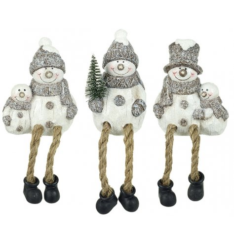 Three smiling sitting snowmen with silver glitter details and long dangling legs.