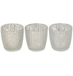 A mix of beautifully decorated glass tlight holders each set with a ridged decal and mottled silver tone to it