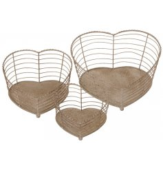 An assorted sized set of heart shaped metal baskets with a distressed natural tone finish