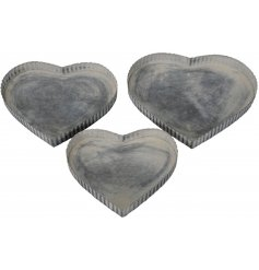 A mix sized set of heart shaped metal trays each decorated with a distressed white washed finish and ridged edge