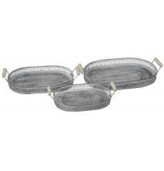 A mix sized set of oval metal trays each decorated with a distressed white washed finish and wooden handles