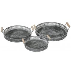 An assorted sized set of round metal trays with distressed finishes and wooden handles