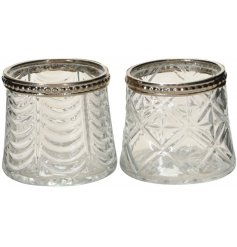 An assortment of clear tlight holders both decorated with ridged decals and silver beaded rims