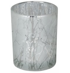 A beautifully decorated frosted glass tlight holder with an etched woodland tree decal surround it