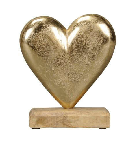 A rustic gold heart decoration set upon a chunky wooden base.