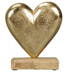 A gold tarnished metal heart on a natural wooden base