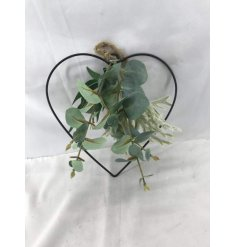 A hanging wire heart entwined with an artificial eucalyptus surrounding it