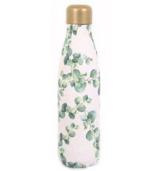 A metal water bottle with a golden toned lid and eucalyptus printed decal