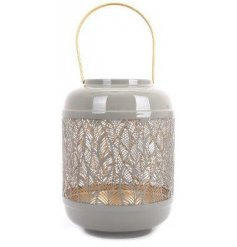 A large metal lantern featuring a feather cut out decal and golden interior tone
