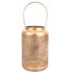 A large metal lantern featuring a golden tone and added intricate cut detailing