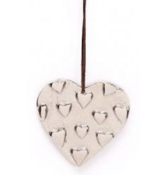 A silver toned hanging metal heart with an added heart embossed feature