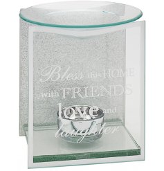 A small glass oil burner with an etched text decal and sparkly background