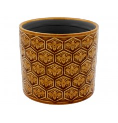 A golden bee, honeycomb patterned planter in a rich honeycomb tone.