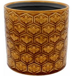 A vintage style planter with a honeycomb and bee pattern for a vintage inspired home.