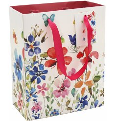 Complete with pretty pink handles, this charming gift bag is covered with colourful flowers and fluttering butterflies