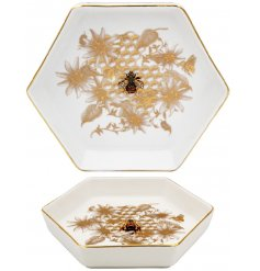 A golden trimmed ceramic trinket dish decorated with a luxe Honeycomb design